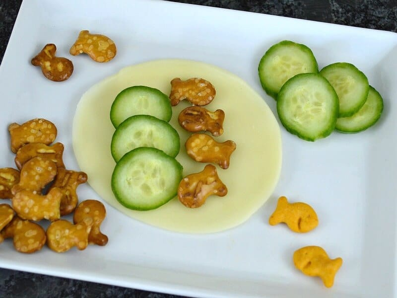 baby cucumber slices with pretzel fish crackers on slice of cheese on white plate
