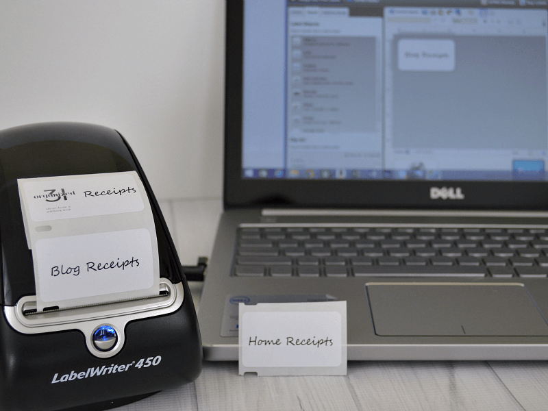label printer next to laptop computer with labels printed out