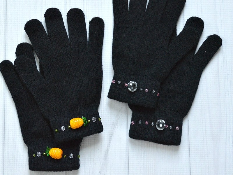 2 black knit gloves decorated with beads on wrists