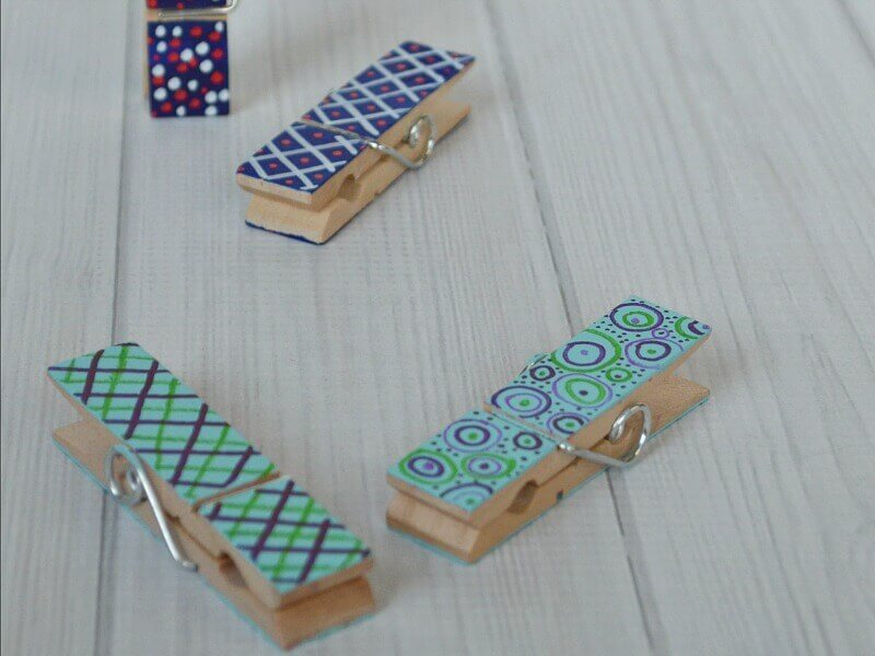4 painted decorated clothes pins on white wood table