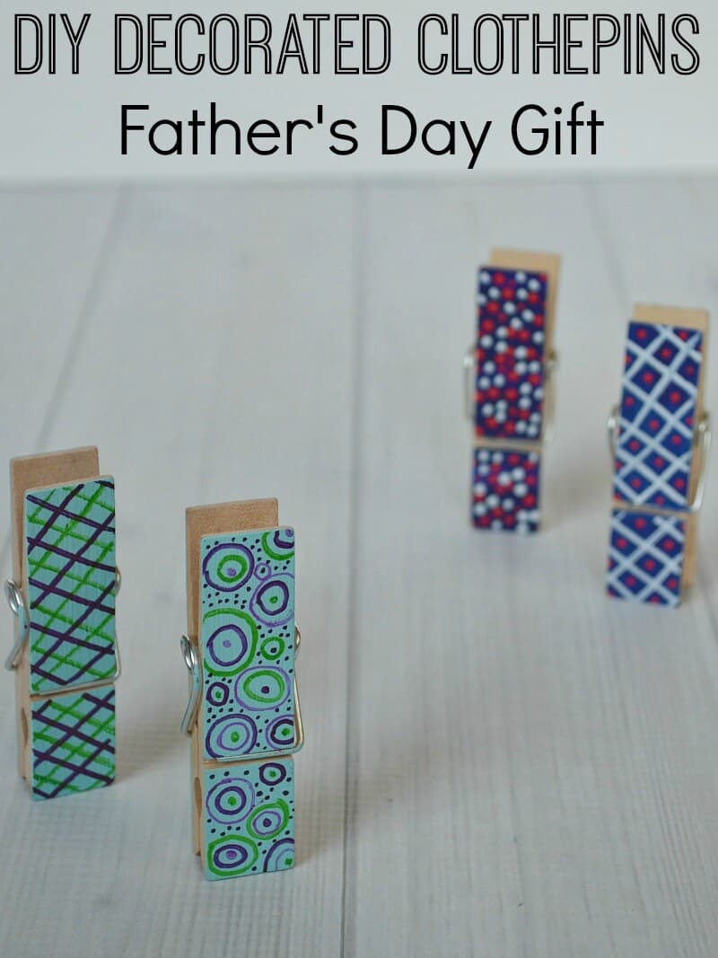 4 clothes pins with painted designs standing up on white wood table