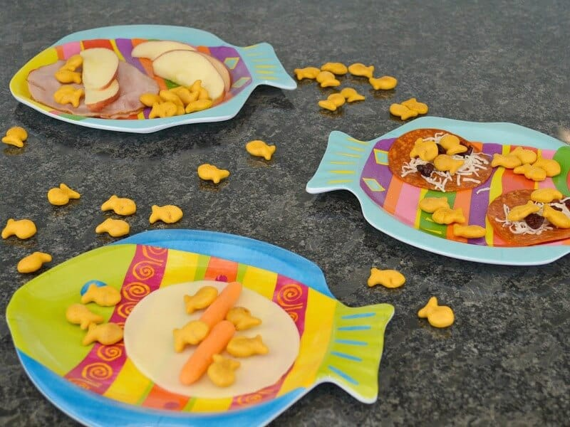 three colorful fish plates with snacks and fish crackers scattered on black counter