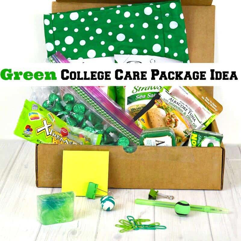 close up of open box filled with green gift items on white wood table