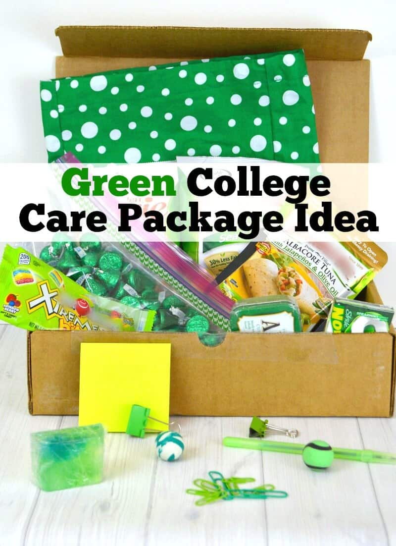 open box filled with green gift and food items and some items spilling out onto table