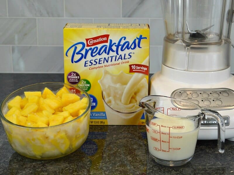 bowl of pineapple chunks, box of breakfast drink, measuring cup of milk and blender on black counter