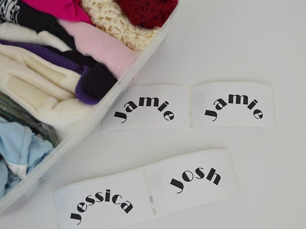 4 white labels with names next to tub with folded items