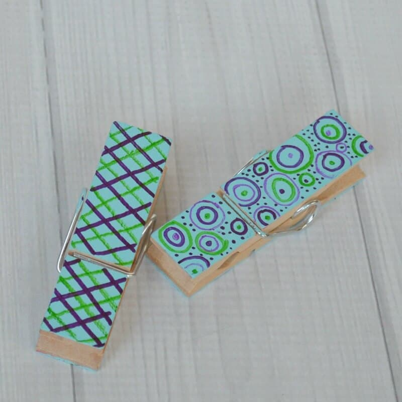 close up of blue and green painted clothes pins on white wood table