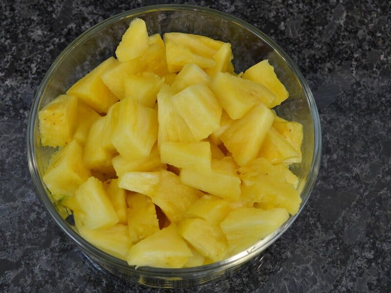 close up of bowl of pineapple chunks in glass bowl on black counter