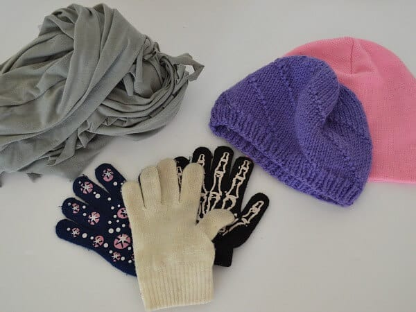 scarf, knit hats and gloves on white table