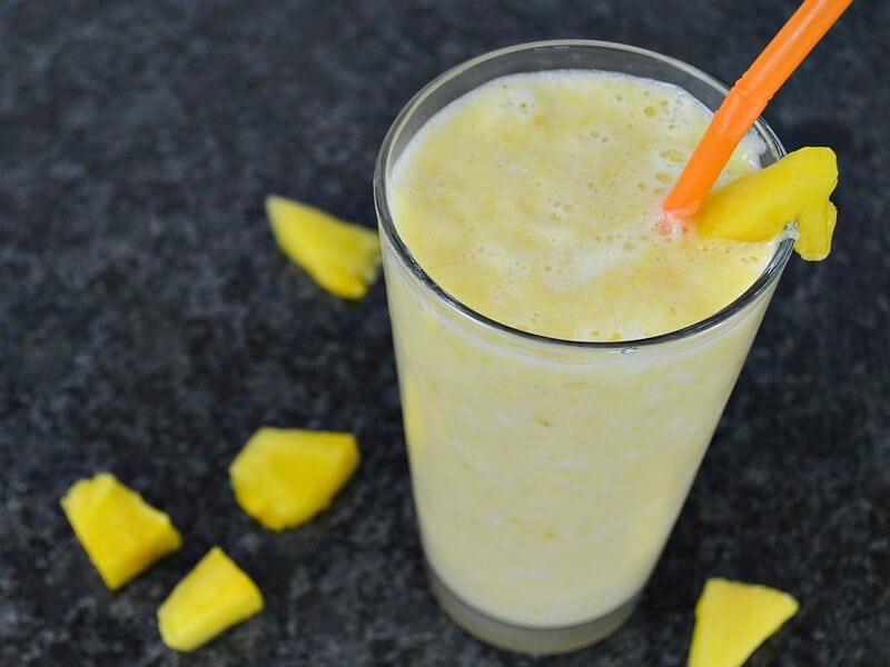 frothy yellow drink in glass with orange straw and pineapple chunks on black counter