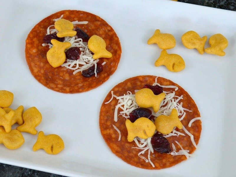 overhead view of fish crackers and shredded cheese on pepperoni on white plate