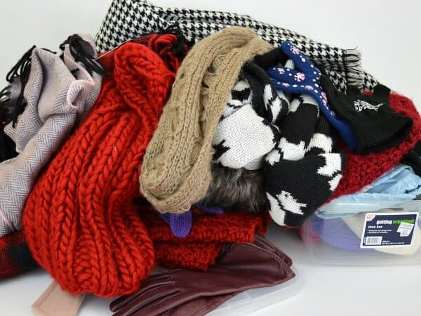 Pile of knit scarves and gloves on white table