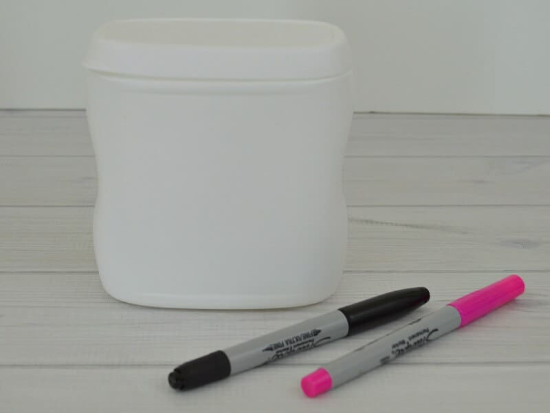 white can with black and pink marker on white wood table