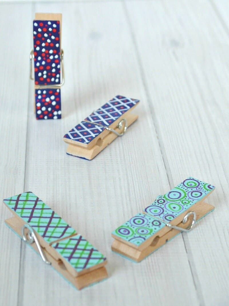 close up of painted clothes pins on white wood table