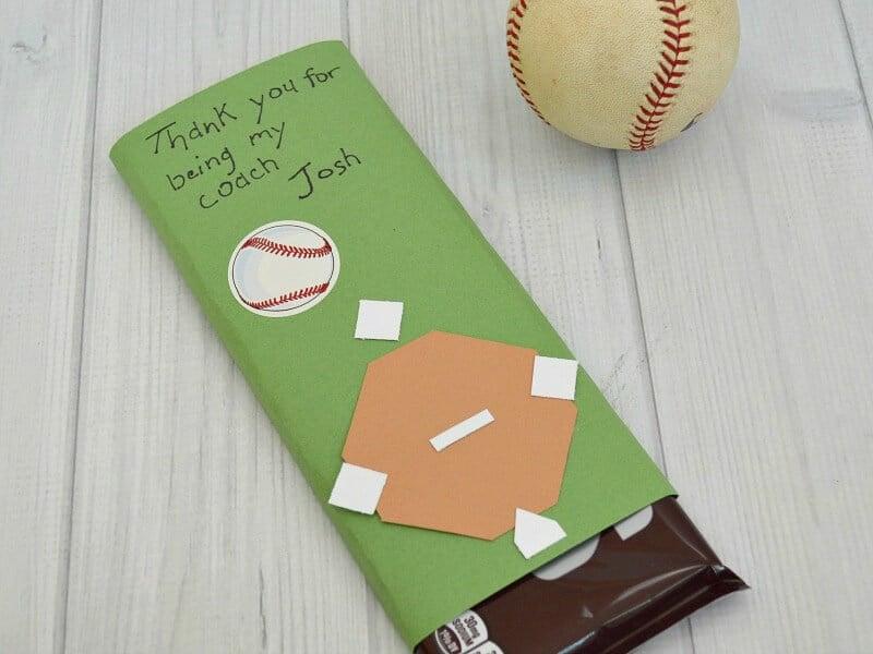candy bar sleeve that looks like baseball diamond laying next to a baseball