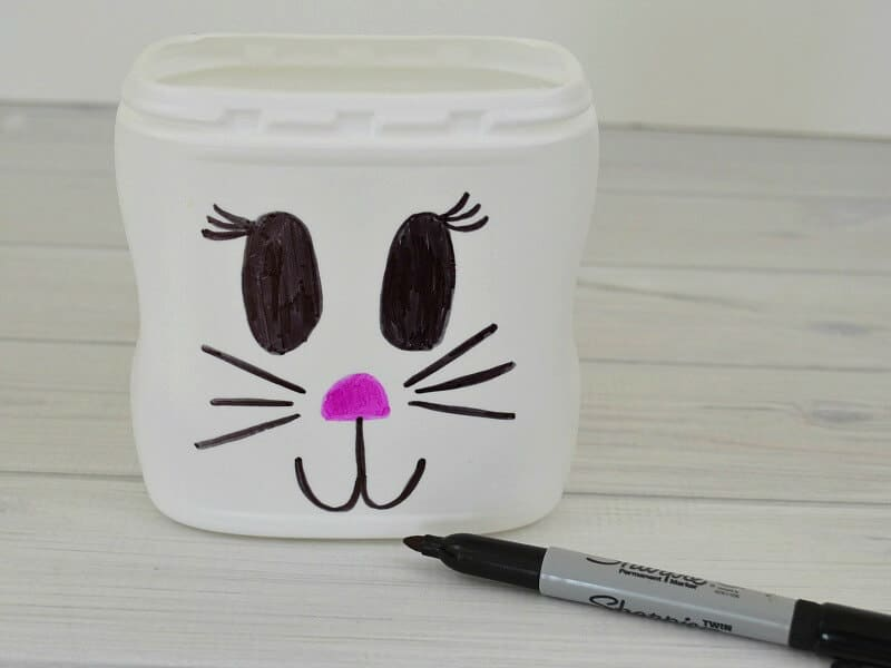 black marker in front of white can with bunny face drawn on it