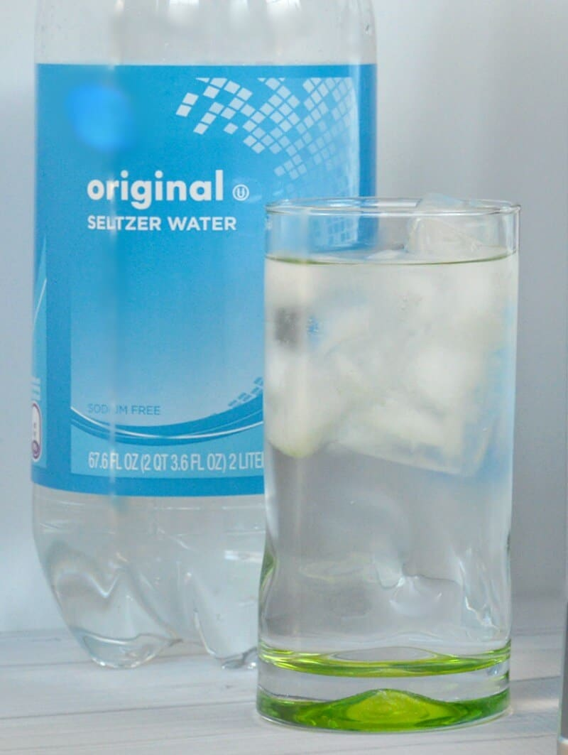 glass of sparkling water next to bottle