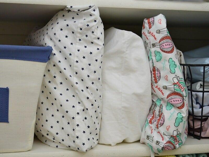 neatly folded sheets filed like books on shelf