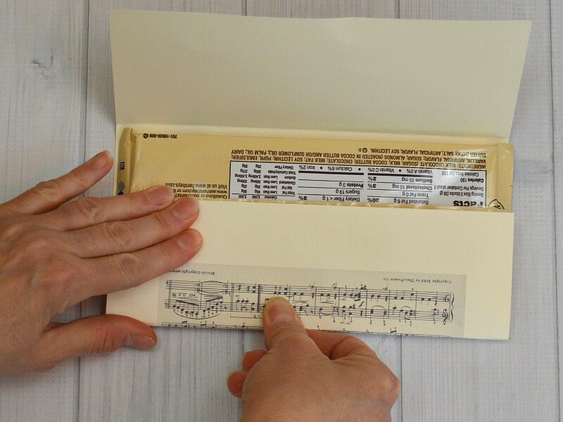 hands wrapping sheet music around a candy bar