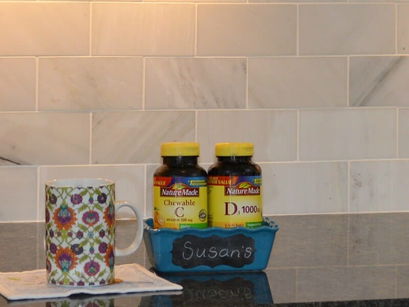 colorful coffee mug next to container holding 2 bottles of vitamins