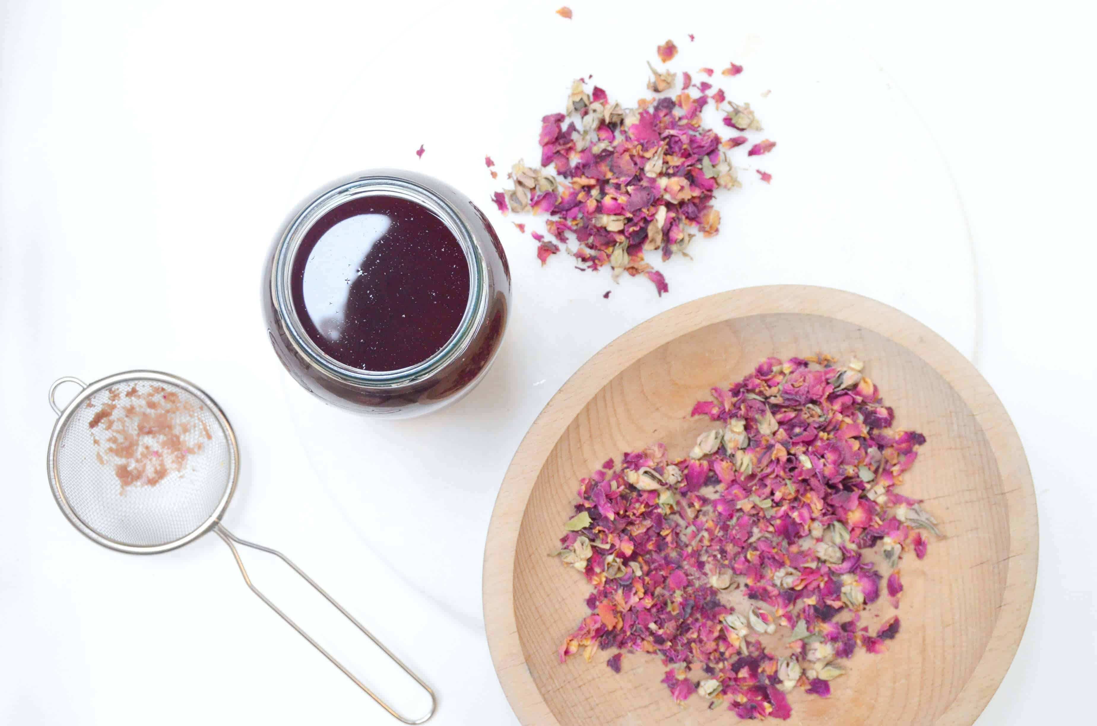 overhead view of flower petals in wood bowl, pile on table and sifter
