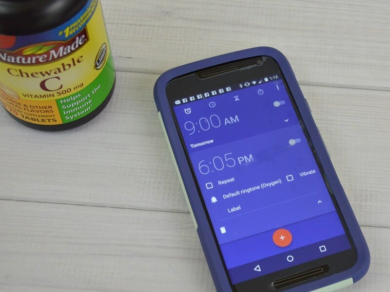 cell phone with alarms set next to bottle of vitamins