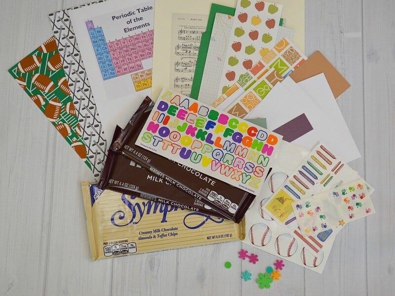 decorative papers and stickers fanned out and stack of large candy bars