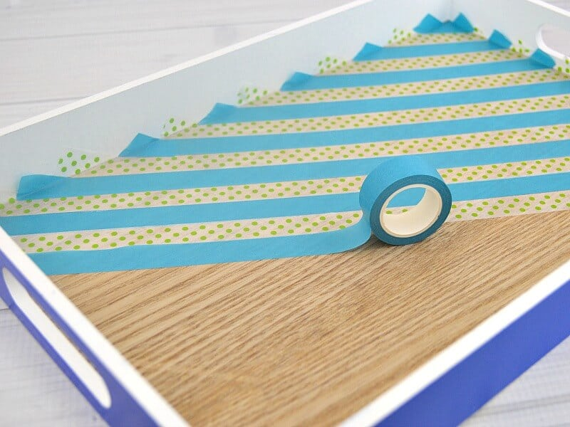 roll of turquoise washi tape making stripes inside blue wood tray