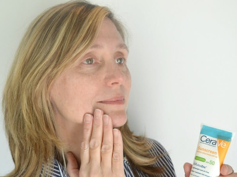 woman holding tube of lotion and rubbing some on her face