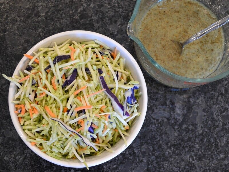 overhead view of shredded cabbage in white bowl next to cup of dressing