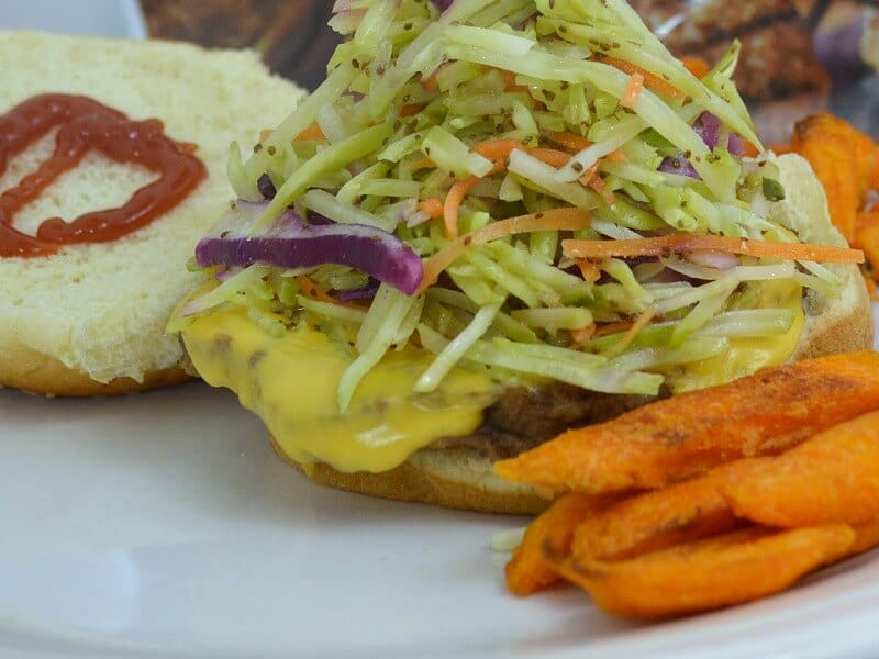 coleslaw on hamburger with fries on white plate