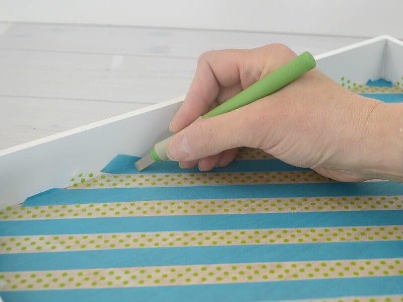 hand with knife cutting edges of washi tape inside the blue tray