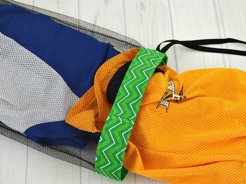 hockey jerseys in black mesh laundry bag with green fabric rim