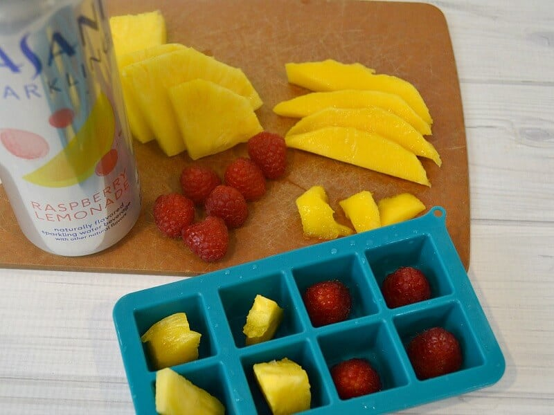 overhead view of fruit on cutting board, fruit in ice cube tray and silver can of sparkling water