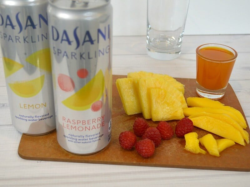 2 silver cans of sparkling water next to fruit cut on cutting board