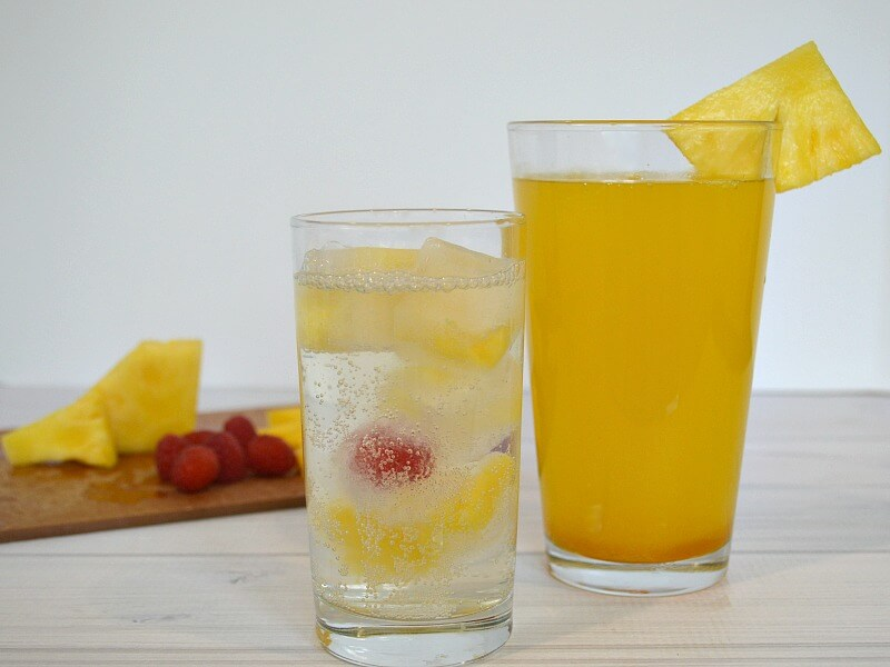 close up of two glasses with drinks and fruit in them and cutting board of fruit in the background