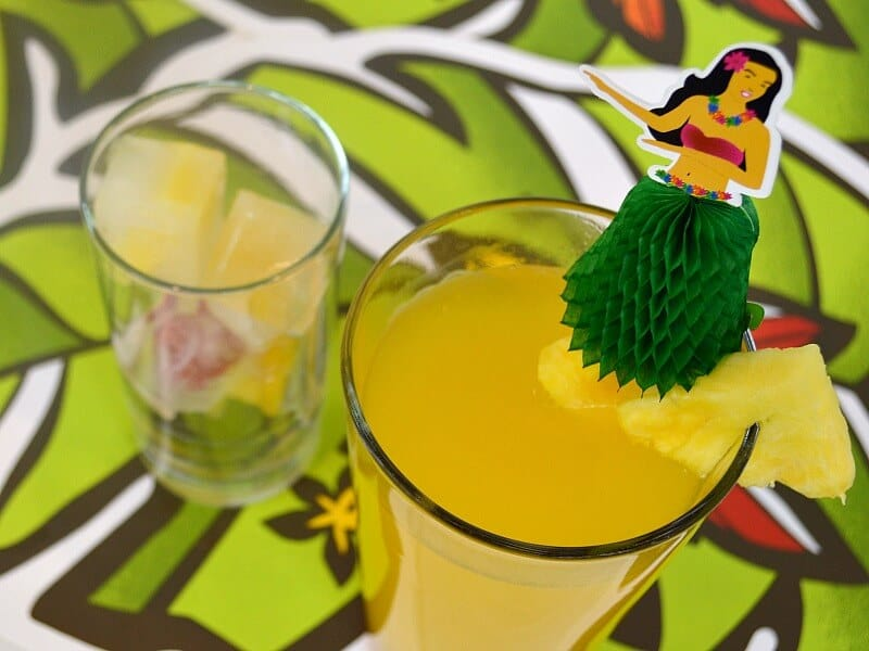 overhead view of 2 glasses with orange drink and hula girl spear with pineapple