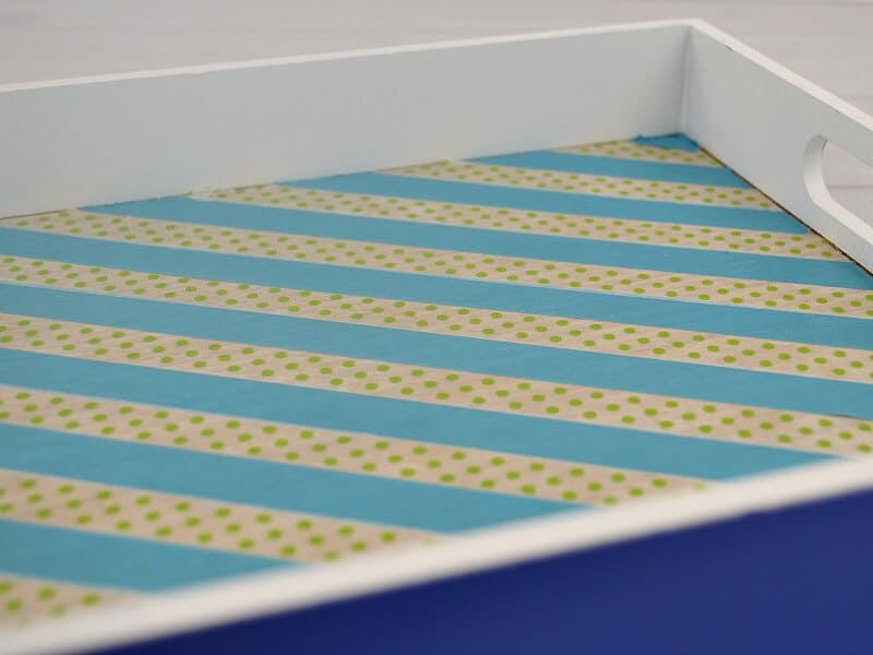 closeup of inside of blue tray with turquoise stripes and green polka dots