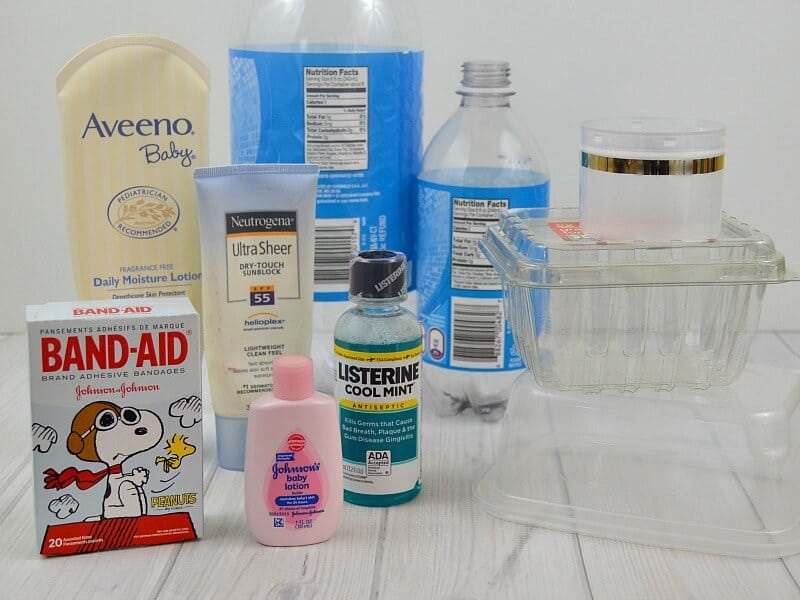 stack of different plastic containers and box of bandages on white table
