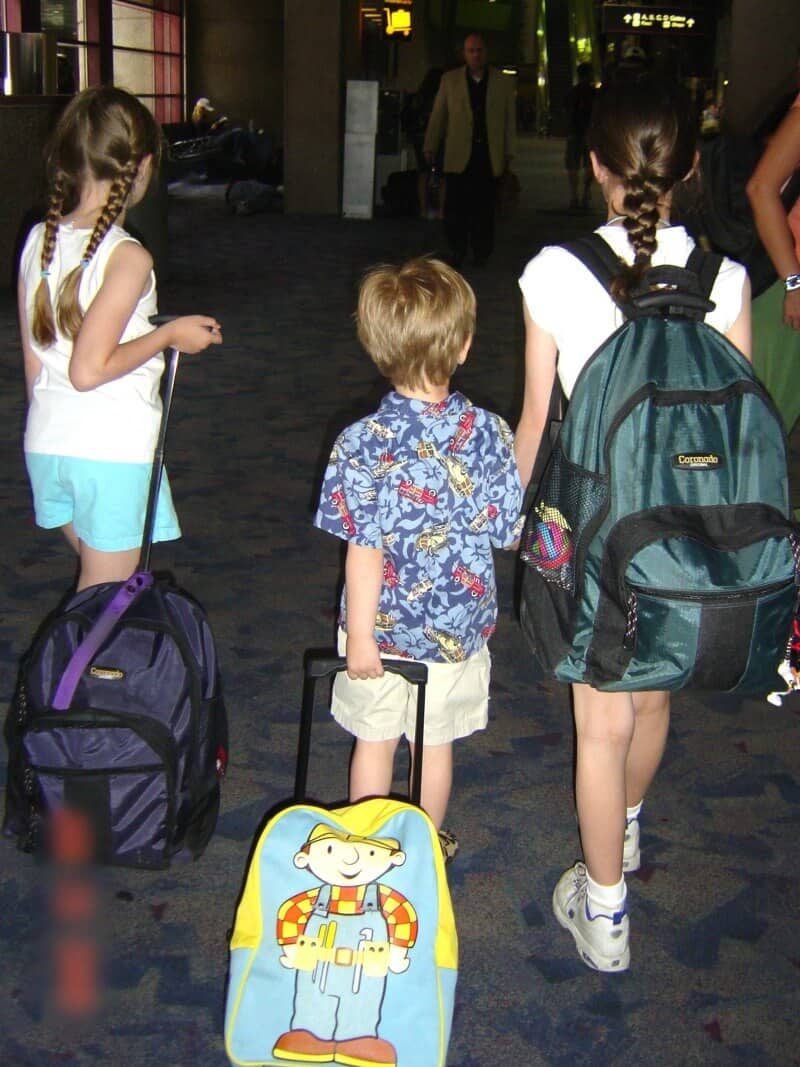 3 children with backpacks walking through airport
