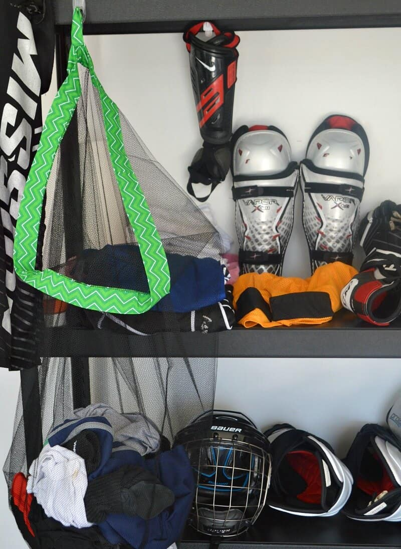 green and black mesh laundry bag hanging on black shelf with hockey equipment