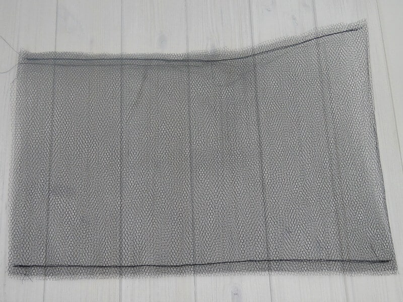 mesh sewn into bag laying on white wood table