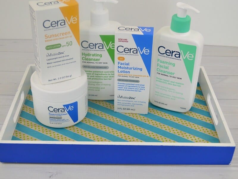 close up of face care products in blue tray on white table