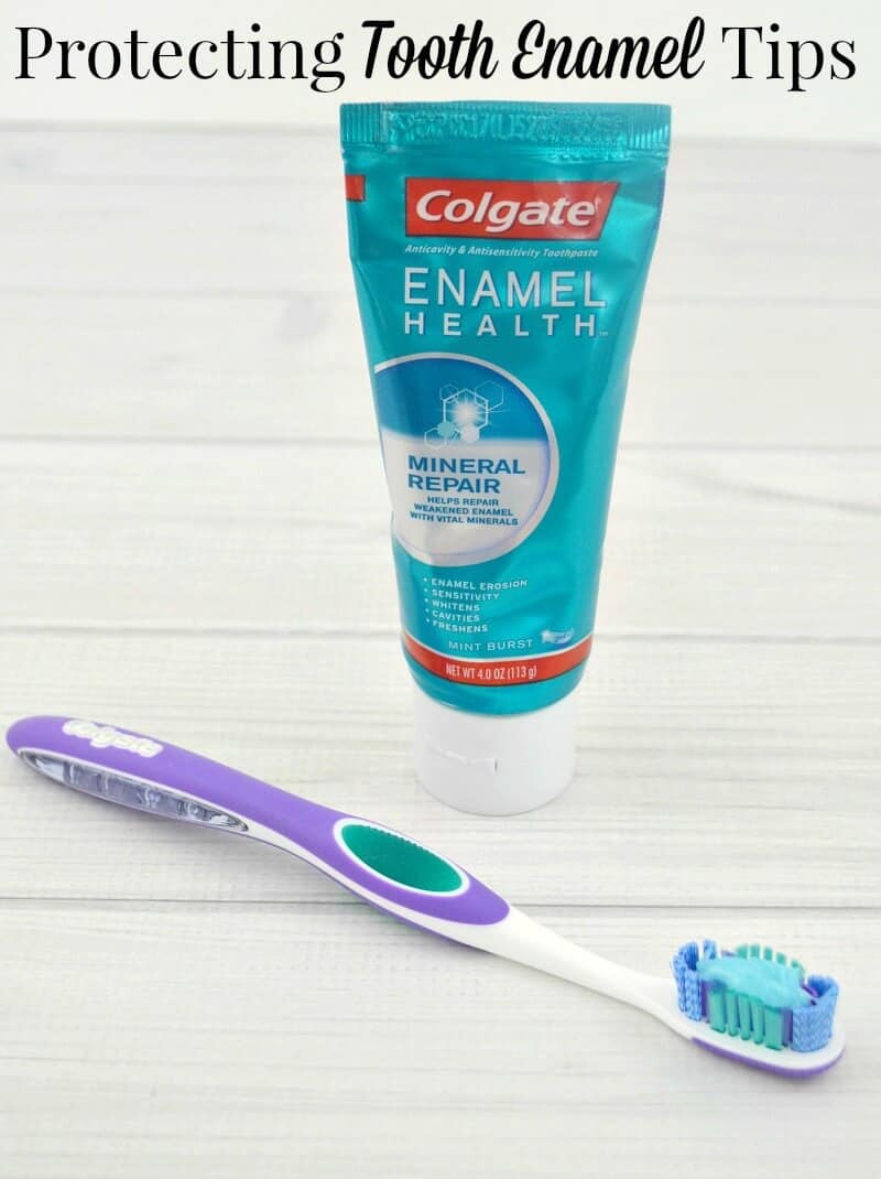 tube of toothpaste next to toothbrush with toothpaste on it on white wood table
