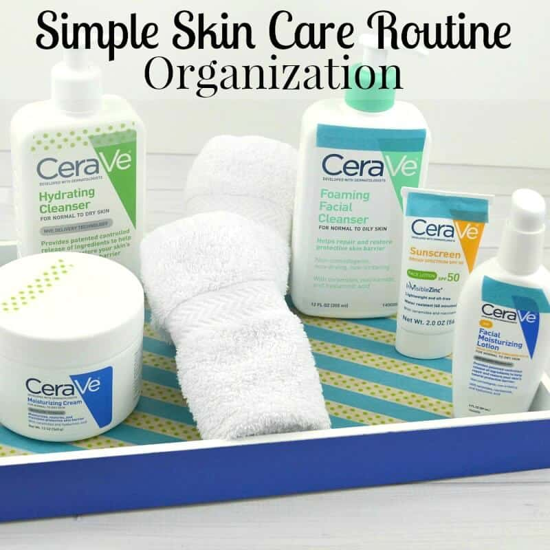 face care products with rolled white washcloths in blue tray on white table