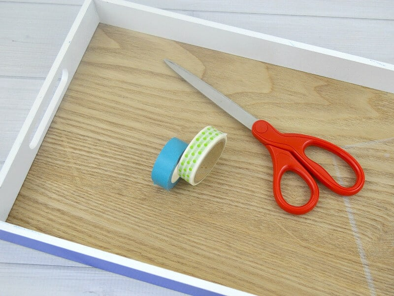 2 rolls of washi tape and pair of scissors inside of wood tray on white wood table