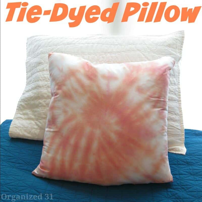 orange swirled tie dyed throw pillow on blue bedspread