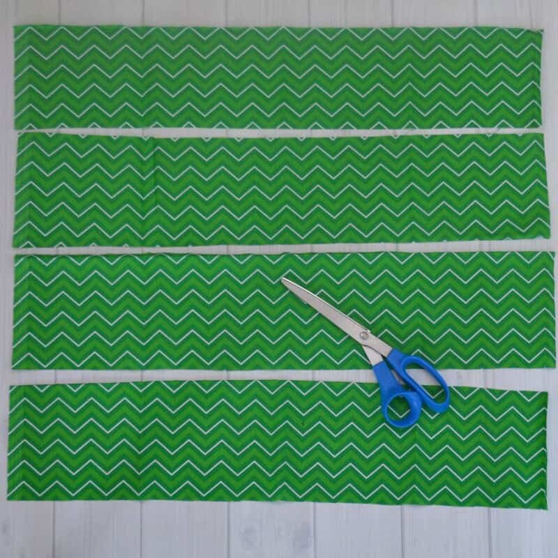 green fabric cut into strips with scissors