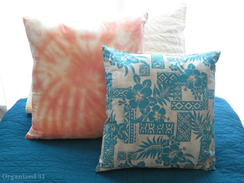 colorful pillows on blue blanket on bed