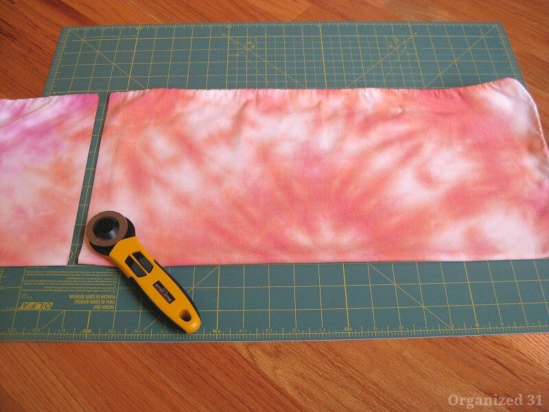 orange tie dyed fabric on green cutting mat with rotary cutter